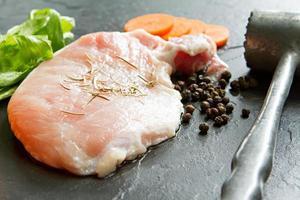 carne di maiale con pepe, rosmarino, carota, sedano e martello di carne. foto