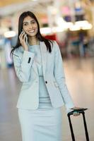 uomo d'affari indiano che fa una telefonata all'aeroporto foto