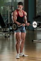 uomo macho sollevamento pesi con bilanciere foto