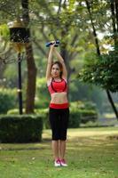 giovane bella donna facendo esercizi di yoga nel parco foto