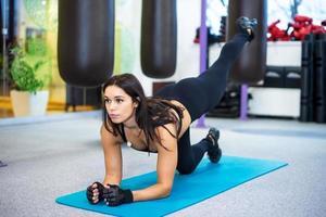donna esile sportiva atletica che fa esercizio di yoga in palestra foto