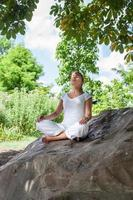 Ragazza bionda 20s meditando sotto un albero su una roccia
