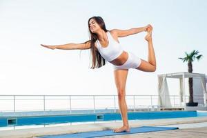 la donna che fa l'allungamento si esercita all'aperto foto