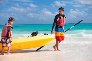 padre e figlio tirando kayak foto