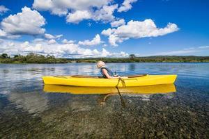 fiume calmo e donna che si distendono in kayak foto