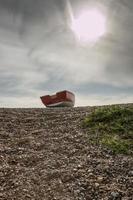 barca a remi abbandonata sulla spiaggia foto