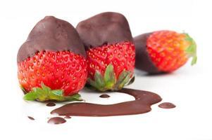 fila di fragole immerse nel delizioso cioccolato foto