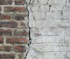 muro di mattoni danneggiato mezzo dipinto di bianco foto