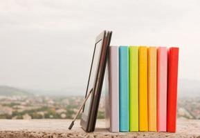 fila di libri colorati con lettore di libri elettronici foto