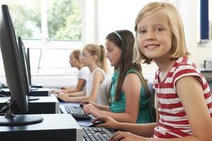 gruppo di bambini delle scuole elementari femminili in classe di computer foto