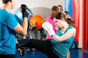 kick boxer femminile con trainer in sparring foto