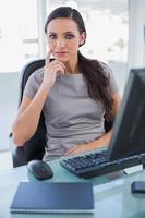 donna di affari premurosa che si siede sulla sua sedia girevole foto