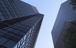 torri moderne dell'ufficio di acciaio e di vetro sotto cielo blu foto