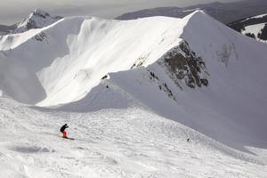 maschio che indossa pantaloni rossi sciare nelle Alpi svizzere foto