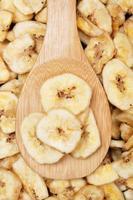 Close up di chips di banane secche su un cucchiaio di legno foto