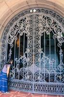 donna che osserva attraverso il cancello del palazzo foto