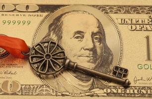 chiave del successo con fiocco rosso sulla banconota in dollari d'oro foto