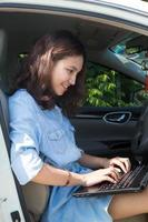 donna asiatica con un computer portatile nella sua auto foto