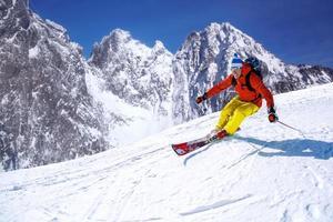 sciatore che scia in discesa in alta montagna contro il tramonto