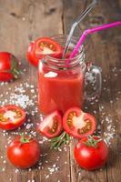 pomodori freschi e un bicchiere di succo di pomodoro foto