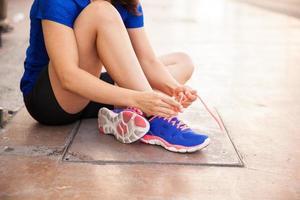 donna che lega i suoi lacci delle scarpe foto