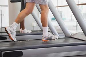 persone in forma corrono su tapis roulant foto