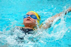 giovane nuotatore nuota dorso foto
