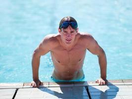 giovane che esce dalla piscina foto