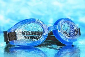 occhialini da nuoto blu con gocce su sfondo azzurro del mare foto