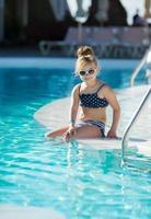 adorabile bambina con gli occhiali da sole a bordo piscina foto