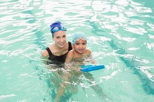 ragazzino sveglio che impara a nuotare con l'allenatore foto