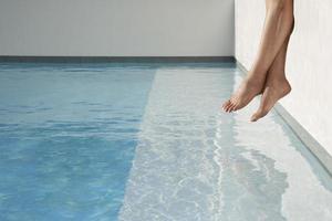 gambe a bordo piscina foto
