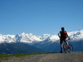 ciclista in mountain-bike che gode di una vista delle alpi foto