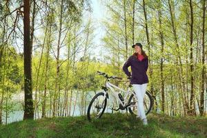 donna in bicicletta nella foresta foto