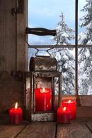 vecchio davanzale in legno decorato con quattro candele rosse di Natale