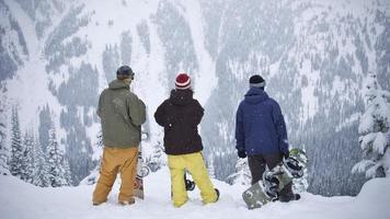 snowboarder che ammirano il fianco di una montagna foto