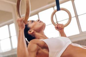 donna forte che fa i pull-up con anelli di ginnastica foto