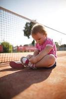 ragazza che impara a legare i lacci delle scarpe foto