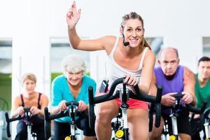gente senior in palestra che si esercita sulla bici di forma fisica foto