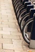 un sacco di biciclette parcheggiate sulla strada della città. foto
