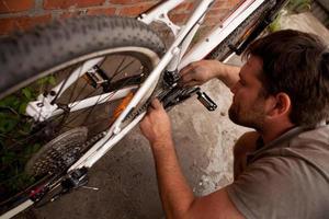 meccanico che ripara una gomma della bicicletta con gli strumenti foto