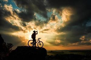 sagoma di un motociclista e bicicletta sullo sfondo del cielo. foto