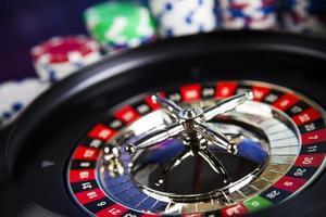 fiches da poker su un gioco con roulette del casinò foto