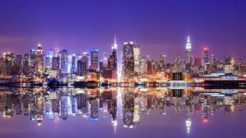 vista dell'acqua dell'orizzonte di Manhattan al crepuscolo con la riflessione foto