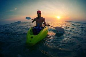 giovane donna che pagaia il kayak foto