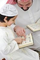 padre arabo e figlio musulmani che recitano il corano foto
