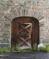 vecchia porta di legno in un muro di pietra del fienile foto