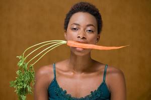 donna con una carota in bocca foto