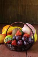 cesto di vimini natura morta con frutta su un tavolo di legno