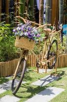 fiori viola su un cestino di bicicletta di bambù. foto